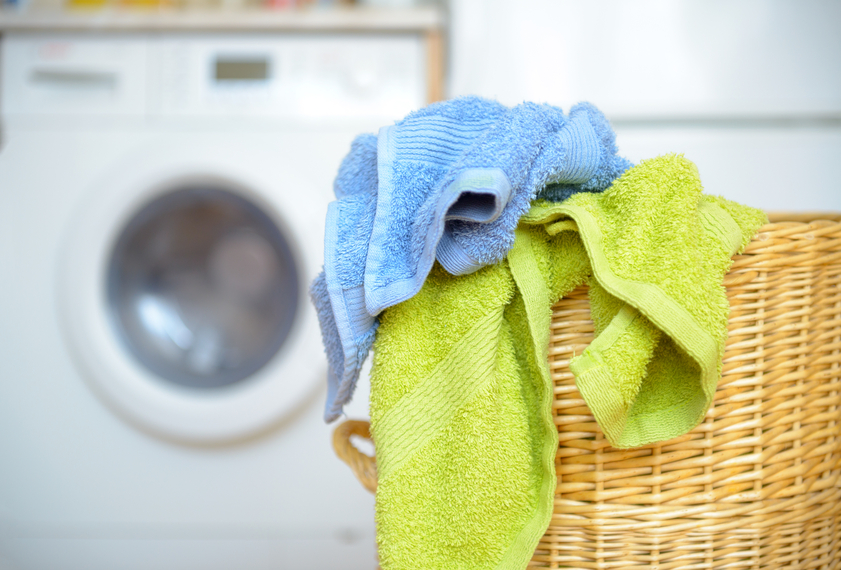 Dirty clothes basket with towels waiting for laundry with washing machine in backround