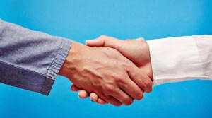 Two business hand shaking hands, as a sign for success, partnership or support, on a blue background.