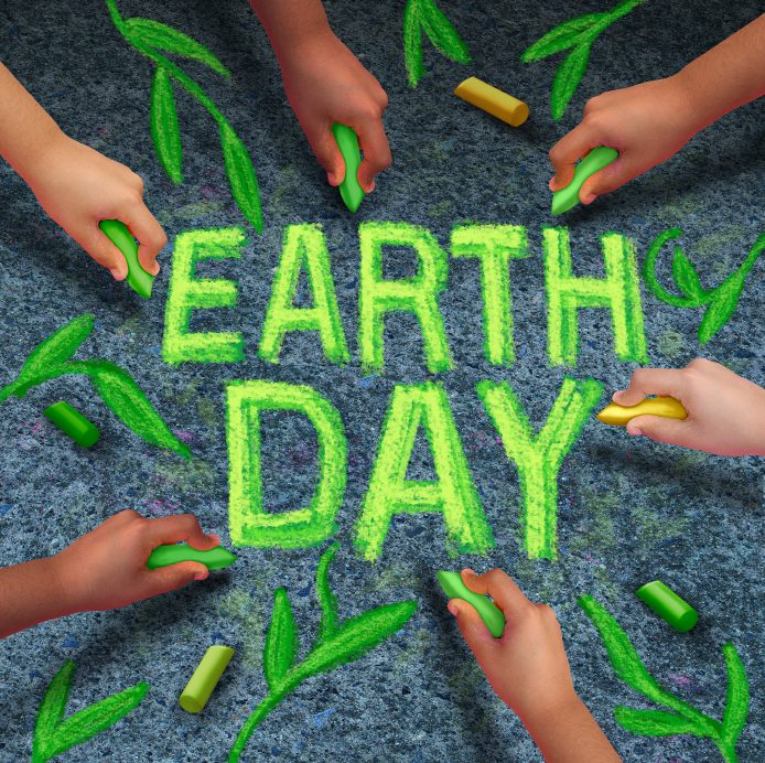 Earth day and environmental protection symbol as a group of diverse ethnic people coming together drawing text and leaves with green chalk on a pavement floor as a global community collaboration to save the planet.