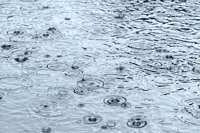 Heavy rain in puddle on sidewalk